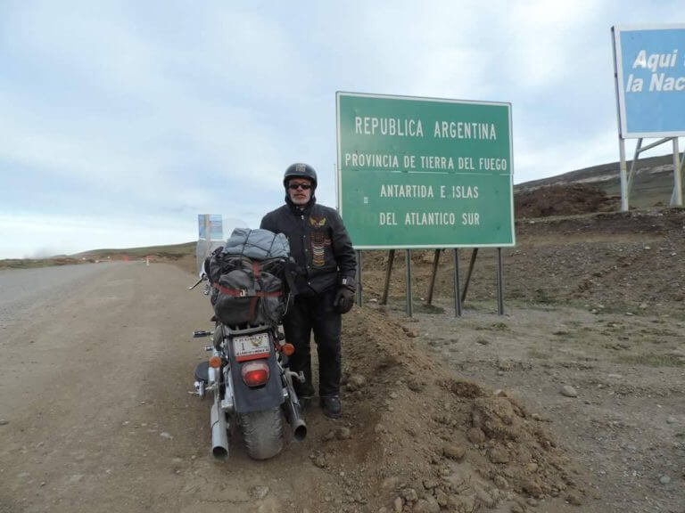 Peace and brotherhood advocate Mario Nieves poses in front of a travel sign in Argentina during his travels to promote peace among nations. Photo courtesy of Mario Nieves
