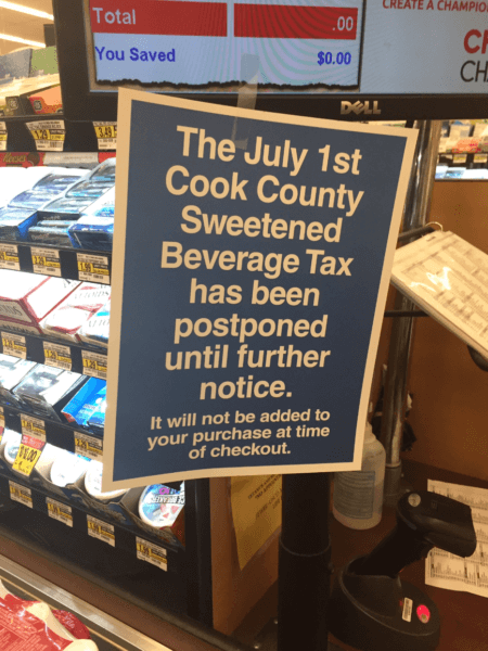 Grocery store sign informing customers in suburban Cook County that the Toni Preckwinkle tax hike on sweetened drinks (Soda) has been delayed because of a court challenge. Photo courtesy of Ray Hanania