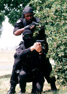 SRA Dave Orth (L) and SRA Clarence Tolliver (R), members of the 60th Security Police Squadron's Base Swat Team, Travis Air Force Base wearing black uniforms stand with M-9 pistols ready behind covering foliage. They are participating in a simulated hostage (Released to Public) (Photo credit: Wikipedia)