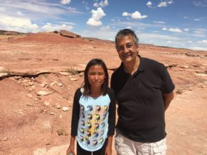 The author with a young Navajo girl who guides tourists at the Dinosaur Tracks a Moenkopi outside Tuba City in Arizona. Photo courtesy of Ray Hanania