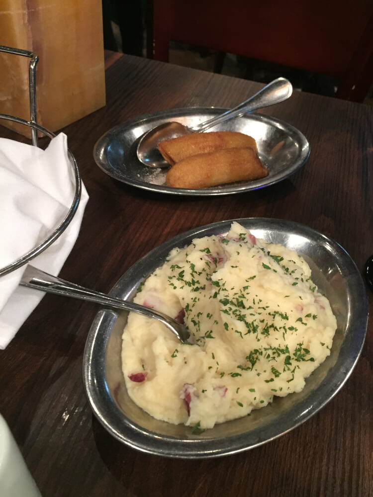 Side dishes mashed potatoes and sweetened bananas at Texas de Brazil rest Woodfield Mall