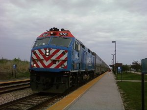 Metra 207 pulls in lightly smoking and hauling 6 cars into Mokena – Hickory Creek station. (Photo credit: Wikipedia)