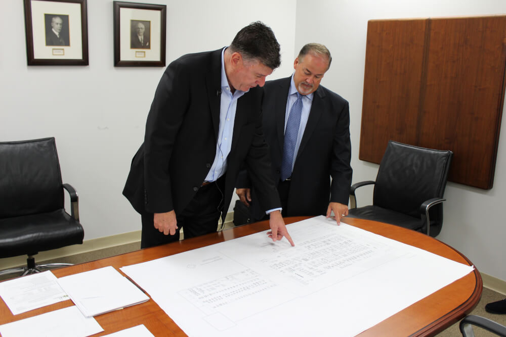 Hart Schaffner Marx (HSM) Chief Operating Officer Ken Ragland (L) and Commissioner Sean Morrison review the floor plans for HSM's new Des Plaines facility.