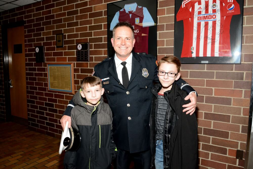 New Bridgeview Fire Lt. Keith Grzadziel poses with his sons at the Bridgeview Village Board meeting on Feb. 6. (Photo by Don Pointer)