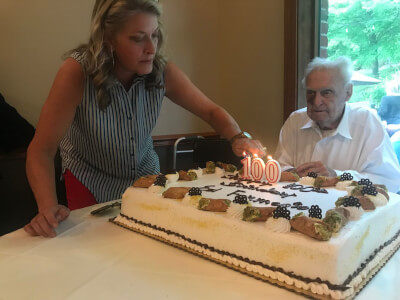 Willow Springs Village Clerk Mary Jane Mannella lights the candles on Ed Formento's 100th birthday cake on July 5. (Photo by Steve Metsch)