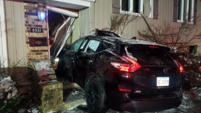 A midsixzed Murano SUV struck a home after crossing 147th Street on Poplar Road in Orland Park in the early morning hours on Saturday. Photo courtesy of the Orland Fire Protection District.