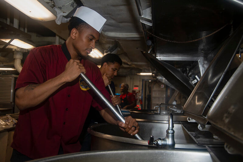 PHOTO CAPTION: 200426-N-ZE328-1089 ATLANTIC OCEAN (April 26, 2020) Culinary Specialist 3rd Class Jeriel Butler, from Chicago, stirs cheese sauce in the aft galley aboard the Nimitz-class aircraft carrier USS Harry S. Truman (CVN 75) in the Atlantic Ocean April 26, 2020. The Harry S. Truman Carrier Strike Group (HSTCSG) remains at sea in the Atlantic as a certified carrier strike group force ready for tasking in order to protect the crew from the risks posed by COVID-19, following their successful deployment to the U.S. 5th and 6th Fleet areas of operation. Keeping HSTCSG at sea in U.S. 2nd Fleet, in the sustainment phase of OFRP, allows the ship to maintain a high level of readiness during the global COVID-19 pandemic. (U.S. Navy photo by Mass Communication Specialist Seaman Kelsey Trinh)