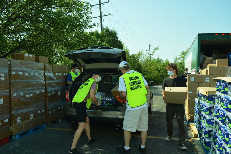 lunteers load a resident's car with free food, water and other necessities during a previous grocery distribution held at Orland Township to assist those experiencing financial difficulties due to the COVID-19 pandemic.