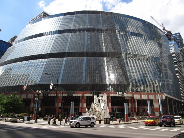 """James R. Thompson Center, Chicago, Illinois (9179428785).jpg More details The James R. Thompson Center (JRTC) is located at 100 W. Randolph Street in the Loop, Chicago, Illinois and houses offices of the State of Illinois. The building opened in May 1985 as the State of Illinois Center. It was renamed in 1993 to honor former Illinois Governor James R. Thompson. The property takes up the entire block bound by Randolph, Lake, Clark and LaSalle Streets, one of the 35 full-size city blocks within Chicago's Loop. In front of the Thompson Center is a sculpture, Monument With Standing Beast, by Jean Dubuffet. The JRTC is sometimes referred to as the State Building. The JRTC was designed by Murphy/Helmut Jahn and opened to mixed reviews by critics, ranging from """"outrageous"""" to """"wonderful"""". The color of the street-level panels was compared to tomato soup. The 17-story, all-glass exterior does not reflect the building's function, and instead conveys an image of pure postmodernism; the effect is striking, especially from the Daley Center.[citation needed] Visitors to the JRTC's interior can see all 17 floors layered partway around the building's immense skylit atrium. The open-plan offices on each floor are supposed to carry the message of """"an open government in action."""" Photo courtesy of Wikipedia"""