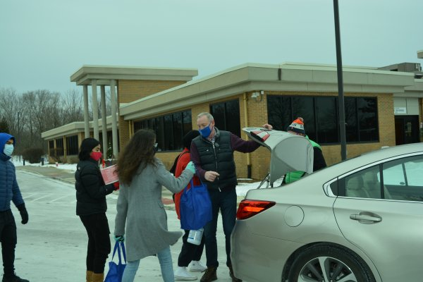 Orland Township Supervisor Paul O'Grady, with the help of students from Andrew and Sandburg high schools, load prepared meals into Township Food Pantry clients' vehicles. The prepared meals were from the Greater Chicago Food Depository's meal production program and distributed to gauge need and interest in the Orland Township community. Photo courtesy of Orland Township