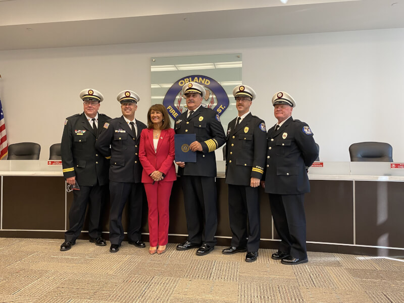 Congresswoman Marie Newman present the Orland Fire Protection District with a copy of a state of praise to be entered into the Congressional Record in September. Newman (center) poses with OFPD Chief Michael Schofield (3rd from left) and the OFPD Battalion Chiefs. Photo courtesy of the Orland Fire Protection District.