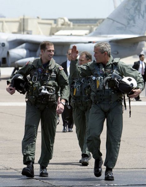 """President George W. Bush walks across the tarmac with NFO Lt. Ryan Phillips to Navy One, an S-3B Viking jet, at Naval Air Station North Island in San Diego Thursday, May 1, 2003. Flying to the USS Abraham Lincoln, the President addressed the nation and declared """"Mission accomplished"""" in Iraq to justify diverting forces from Afghanistan. Photo courtesy of Wikipedia"""